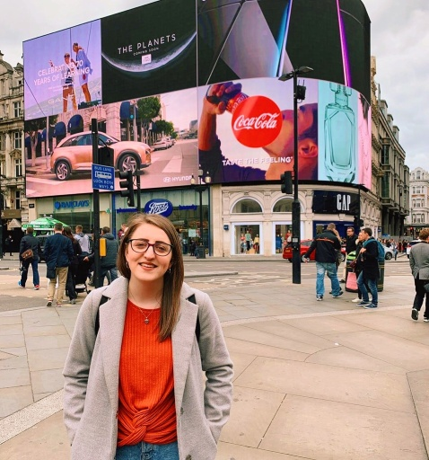 A girl standing in front of Piccadilly Circus in London